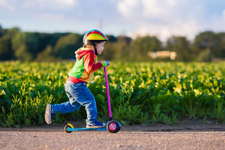 Little child learning to ride a scooter in a city park on sunny summer day. Cute preschooler boy in safety helmet riding a roller. Kids play outdoors. Active leisure and outdoor sport for children. Stock Photo