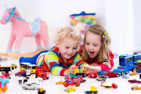 mess: Little toddler boy and girl playing with model car collection on the floor. Transportation and rescue toys for children. Toy mess in child room. Many cars for little boys. Educational games for kids.