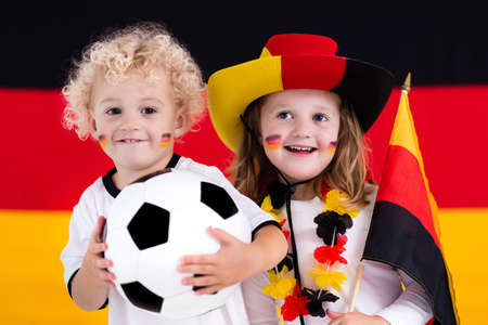 Children cheering and supporting German national football team. Kids fans and supporters of Germany during soccer championship.