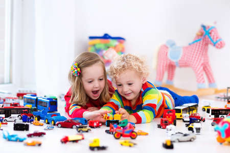 siblings: Little toddler boy and girl playing with model car collection on the floor. Transportation and rescue toys for children. Toy mess in child room. Many cars for little boys. Educational games for kids.