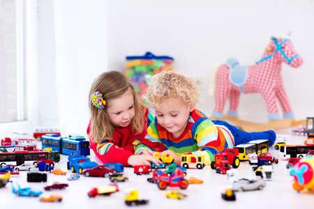 habitacion desordenada: El pequeño niño chico y chica jugando con la colección del modelo del coche en el suelo. juguetes de transporte y salvamento para niños. desorden de juguetes en la habitación del niño. Muchos coches para los niños pequeños. juegos educativos para niños. Foto de archivo