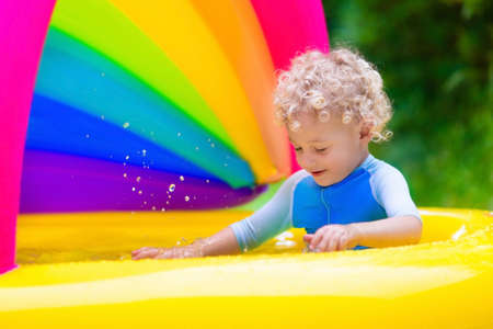 Children playing in inflatable baby pool. Kids swim and splash in colorful garden play center. Happy little boy playing with water toys on hot summer day. Family having fun outdoors in the backyard. Stock Photo