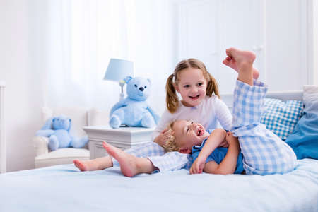 kids wear: Happy kids playing in white bedroom. Little boy and girl, brother and sister play on the bed wearing pajamas. Nursery interior for children. Nightwear and bedding for baby and toddler. Family at home.