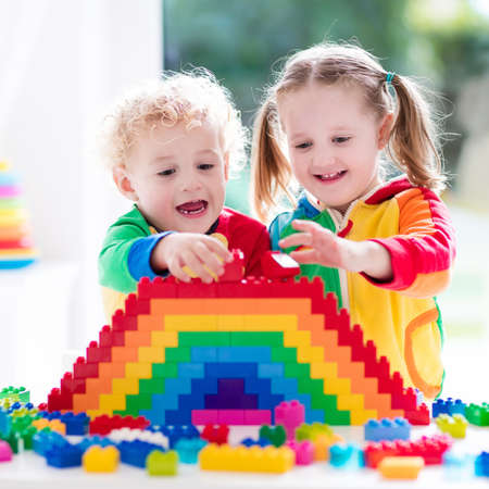 play blocks: Child playing with colorful toys. Little girl and funny curly baby boy with educational toy blocks. Children play at day care or preschool. Mess in kids room. Toddlers build a tower in kindergarten. Stock Photo