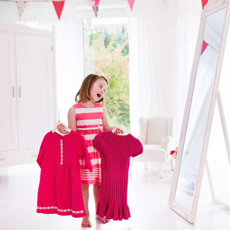 reflection mirror: Little girl choosing dresses in white bedroom. Child watching mirror reflection holding pink dress choosing outfit. Girls nursery.  Shopping clothing for kids. Dressing room interior for children.