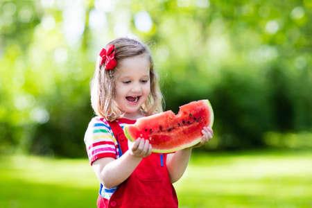 comiendo frutas: Niño que come la sandía en el jardín. Los niños comen fruta al aire libre. merienda saludable para los niños. Niña que juega en el jardín muerde una rebanada de melón de agua.
