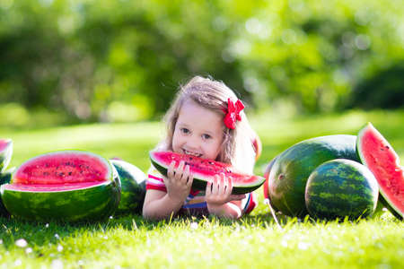 water melon: Child eating watermelon in the garden. Kids eat fruit outdoors. Healthy snack for children. Little girl playing in the garden biting a slice of water melon.