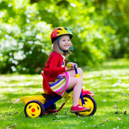 baby playing toy: Cute girl wearing safety helmet riding her tricycle in sunny summer park. Kids ride bicycle. First bike for little child. Active toddler kid playing and cycling outdoors. Kids play in the garden. Stock Photo