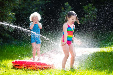 sprinkler: Little girl and boy playing with garden water slide. Children jumping and splashing with gardening hose. Outdoor summer fun with backyard sprinkler for kids on hot sunny day.