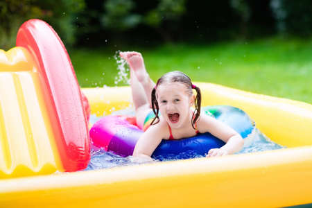 family playing: Children playing in inflatable baby pool. Kids swim and splash in colorful garden play center. Happy little girl playing with water toys on hot summer day. Family having fun outdoors in the backyard.