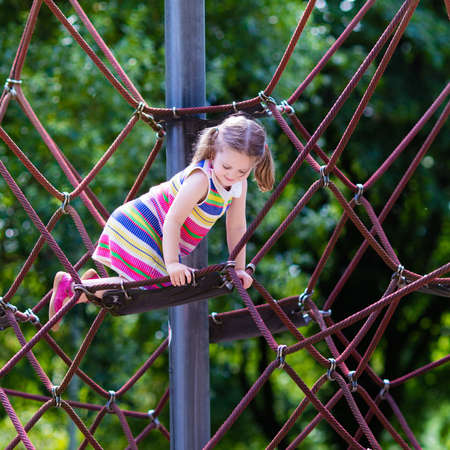 climb: Active little child playing on climbing net and jumping on trampoline at school yard playground. Kids play and climb outdoors on sunny summer day. Cute girl on nest swing at preschool sport center. Stock Photo