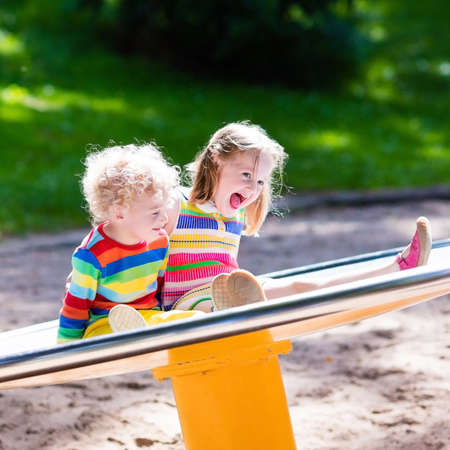 play ground: Little boy and girl on a playground. Child playing outdoors in summer. Kids play on school yard. Happy kid in kindergarten or preschool. Children having fun at daycare play ground. Toddler on a swing.