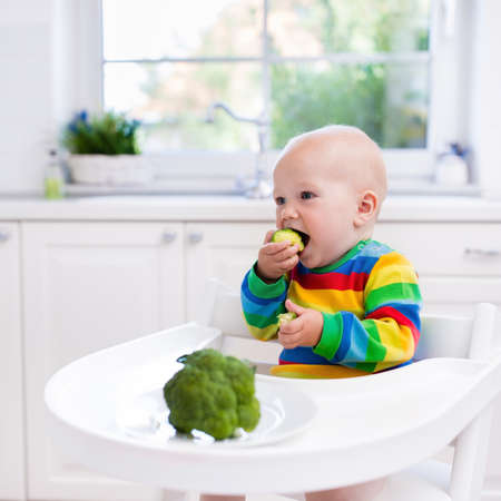 solid food: Happy baby sitting in high chair eating broccoli in a white kitchen. Healthy nutrition for kids. Bio vegetable as solid food for infant. Children eat vegetables. Little boy having lunch at home.