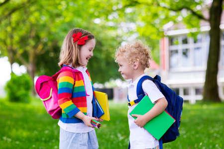 Kind naar school gaan. Jongen en meisje houdt van boeken en potloden op de eerste schooldag. Kleine studenten opgewonden om terug naar school te gaan. Begin van de les na de vakantie. Kinderen eten appel in schoolplein Stockfoto