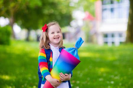 školačka: Šťastné dítě drží tradiční německé bonbón kužel na první školní den. Malý student s batohem a knihy nadšený, že zpátky do školy. Začátek třídy v Německu s sladkostí pro děti.