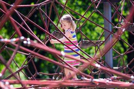 niño escalando: niño activo que juega en la red de escalada y el salto en el trampolín en el patio patio de la escuela. Los niños juegan y suben al aire libre en un día soleado de verano. linda chica en el columpio nido en el centro deporte preescolar.