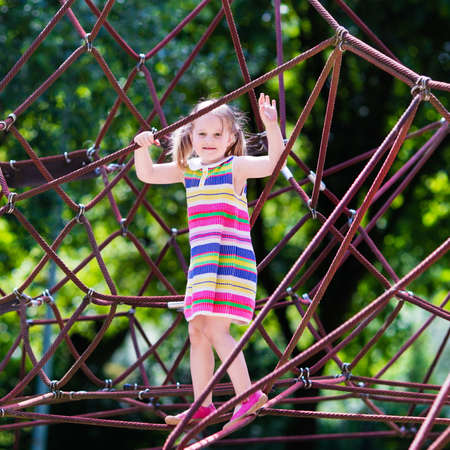 school yard: Active little child playing on climbing net and jumping on trampoline at school yard playground. Kids play and climb outdoors on sunny summer day. Cute girl on nest swing at preschool sport center. Stock Photo