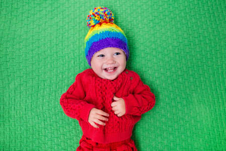 Cute baby in warm wool knitted hat on a red blanket. Autumn and winter clothing for young kids. Colorful knitwear for children. Adorable little boy ready for a walk on a cold fall day. Stock Photo