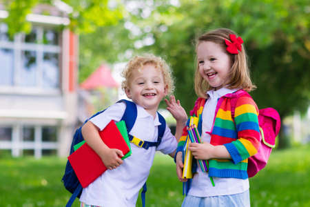 Ребенок идет в школу. Мальчик и девочка держит книги и карандаши на первый день школы. Маленькие студенты возбуждены, чтобы вернуться в школу. Начало класса после отпуска. Дети едят яблоко в школьном дворе Фото со стока