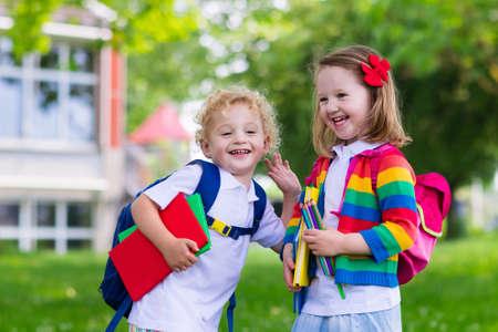 아이가 학교에가는. 소년과 소녀는 학교 첫날에 책과 연필을 들고. 어린 학생들은 다시 학교로 흥분. 휴가 후 수업의 시작. 학교 마당에 사과를 먹는 아 스톡 콘텐츠