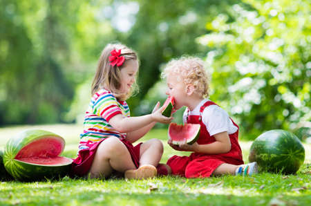 preschooler: Child eating watermelon in the garden. Kids eat fruit outdoors. Healthy snack for children. Little girl and boy playing in the garden biting a slice of water melon.