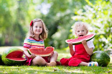 comiendo frutas: Niño que come la sandía en el jardín. Los niños comen fruta al aire libre. merienda saludable para los niños. Niña y niño jugando en el jardín muerde una rebanada de melón de agua.