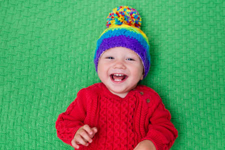 kids wear: Cute baby in warm wool knitted hat on a red blanket. Autumn and winter clothing for young kids. Colorful knitwear for children. Adorable little boy ready for a walk on a cold fall day. Stock Photo