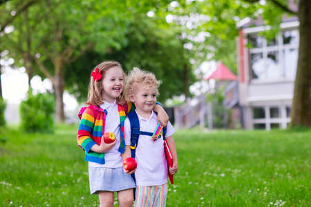 first day: Child going to school. Boy and girl holding books and pencils on the first school day. Little students excited to be back to school. Beginning of class after vacation. Kids eating apple in school yard