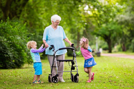 grand kids: Happy senior lady with a walker holding hands of little boy and girl. Grandmother with grand children enjoy a walk in summer park. Kids supporting disabled grandparent.