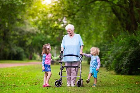 Gelukkige hogere dame met een rollator, hand in hand van de kleine jongen en meisje. Grootmoeder met kleinkinderen genieten van een wandeling in de zomer park. Kids ondersteunende grootouder uitgeschakeld.