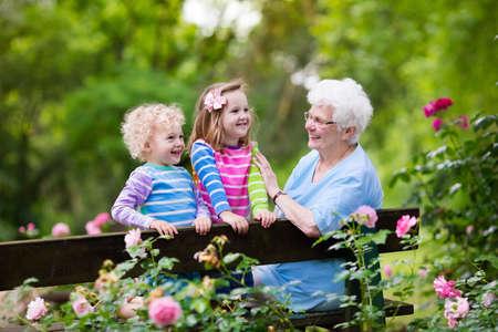 Signora maggiore felice gioca con il piccolo ragazzo e ragazza in giardino di fioritura rosa. Nonna con nipoti seduti su una panchina nel parco estate con bellissimi fiori. Bambini giardinaggio con nonni.