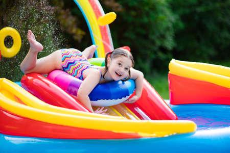 petite fille maillot de bain: Enfants jouant dans la piscine gonflable bébé. Les enfants nagent et éclaboussent dans le centre de jeux colorée de jardin. Bonne petite fille jouant avec des jouets d'eau sur chaude journée d'été. Famille amuser à l'extérieur dans la cour.