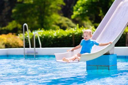 schwimmring: Glücklicher lachender kleiner Junge spielt auf Wasserrutsche im Freibad an einem heißen Sommertag. Kinder schwimmen lernen. Kind tragen Sonnenschutz Hautausschlag Wache Gleiten auf Aqua Spielplatz in tropischen Resort