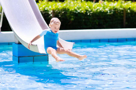slide: Happy laughing little boy playing on water slide in outdoor swimming pool on a hot summer day. Kids learn to swim. Child wearing sun protection rash guard sliding on aqua playground in tropical resort