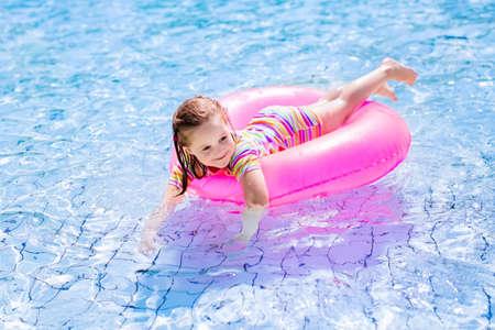 maillot de bain fille: Bonne petite fille jouant avec anneau gonflable coloré dans la piscine extérieure sur chaude journée d'été. Les enfants apprennent à nager. Enfants portant protection solaire éruption garde de détente dans la station tropicale