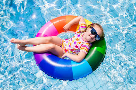 Happy little girl playing with colorful inflatable ring in outdoor swimming pool on hot summer day. Kids learn to swim. Children wearing sun protection rash guard relaxing in tropical resort Stock Photo - 61029554