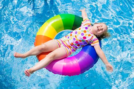 Šťastný holčička hraje s barevnými nafukovacím kruhu ve venkovním bazénu v horkém letním dni. Děti se učí plavat. Děti nosí ochranný sluneční vyrážka stráž relaxaci v tropických rekreačních