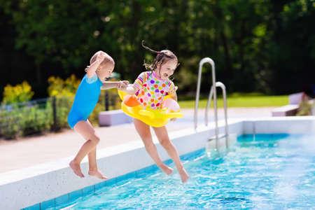 행복 한 작은 소녀와 소년 가족 여름 휴가 동안 열 대 리조트 야외 수영장으로 점프 손을 잡고. 수영을 배우는 아이들. 소년에 초점.