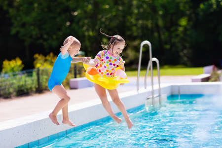 Happy little girl and boy holding hands jumping into outdoor swimming pool in a tropical resort during family summer vacation. Kids learning to swim. Focus on boy. Banco de Imagens - 61029549