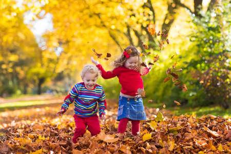 Niños felices jugando en el hermoso parque del otoño en día cálido y soleado de la caída. Los niños juegan con las hojas de arce de oro. Centrarse en la niña Foto de archivo - 60370276