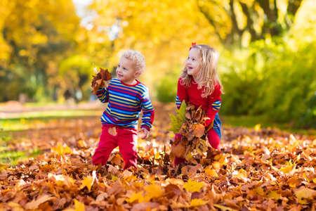 hermanos jugando: niños felices jugando en el hermoso parque del otoño en día cálido y soleado de la caída. Los niños juegan con las hojas de arce de oro.