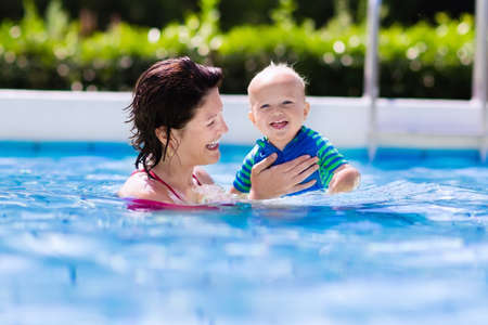 swim: Happy young mother playing with her baby in outdoor swimming pool on hot summer day. Kids learn to swim during family vacation. Children wearing sun protection rash guard relaxing in tropical resort
