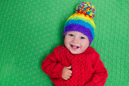 baby face: Cute baby in warm wool knitted hat on a red blanket. Autumn and winter clothing for young kids. Colorful knitwear for children. Adorable little boy ready for a walk on a cold fall day. Stock Photo