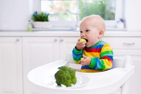 Gelukkig baby zittend in hoge stoel eten van broccoli in een witte keuken. Gezonde voeding voor kinderen. Bio plantaardige als vast voedsel voor baby. Kinderen groenten eten. Jongetje lunchen thuis.