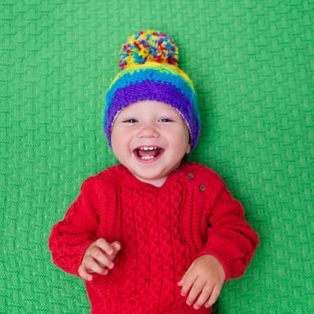 bobble: Cute baby in warm wool knitted hat on a red blanket. Autumn and winter clothing for young kids. Colorful knitwear for children. Adorable little boy ready for a walk on a cold fall day. Stock Photo