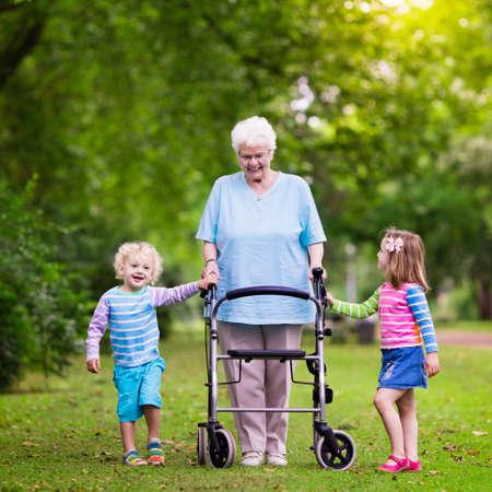 Señora mayor feliz con un andador de la mano del niño y niña. Abuela con nietos disfrutar de un paseo en el parque de verano. Niños de apoyo abuelos discapacitados. Foto de archivo