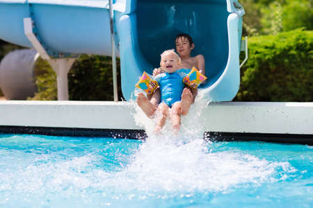beautiful boys: Happy boys, two brothers having fun together on water slide in a swimming pool during summer vacation in a beautiful tropical resort. Children sliding and playing in aqua park.