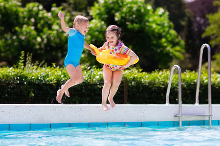 Happy little girl and boy holding hands jumping into outdoor swimming pool in a tropical resort during family summer vacation. Kids learning to swim. Water fun for children.