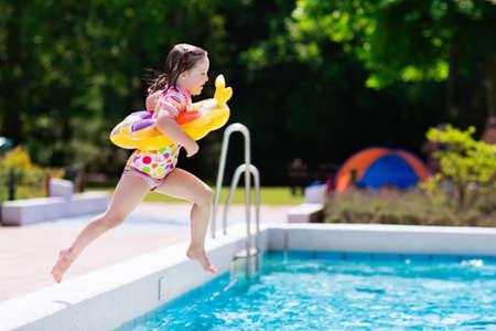 Bambina felice con l'anello giocattoli gonfiabili salto in piscina esterna in una località tropicale durante le vacanze estive della famiglia. I bambini imparano a nuotare. divertimento acquatico per bambini.