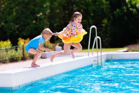 행복 한 작은 소녀와 소년 가족 여름 휴가 동안 열 대 리조트 야외 수영장으로 점프 손을 잡고. 수영을 배우는 아이들. 아이들을위한 재미있는 물. 스톡 콘텐츠